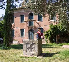 Boy on Torcello (UrbanphotoZ) Tags: venice boy italy orange house tree green stone bottle sitting cross balcony lawn tshirt denver plaster shutters venezia torcello veneto