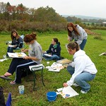 Students sit outside and paint the nature around them.
