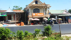 To the cafe (Roving I) Tags: architecture cycling construction bricks motorcycles villages vietnam bicycles roads umbrellas cafes schoolboys langco