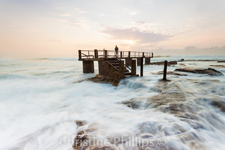 Uvong Beach South Africa - Pier with fisherman at sunrise on a stormy morning