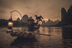 Cormorant fisherman... (Syahrel Azha Hashim) Tags: singleexposure mountains tokina shallow simple dramaticsky guilin touristattraction sunset conventional humaninterest handheld colorimage vacation destination china moment fishing d300s elder smoking uwa mountain portrait lantern expression water unique 11mm chinese details portraiture xingping ultrawideangle bird local traditional dof bamboo oneperson single detail nikon getaway liriver elite holiday clouds culture traditionalclothing light fishermen naturallight scene colorful iconic cormorants travel syahrel river birds colors paddle bambooraft hat oldman fisherman