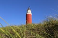 The lighthouse Eierland on the Northern tip of Texel (B℮n) Tags: texel lighthouseoftexel dunesoftexelnationalpark vuurtorenvantexel schotsehooglanders highlandcattle dunes dutchisland islandoftexel mooitexel kyloe scottishbreed cocksdorp moon vuurtoren eierland sooc red rood lighthouse breeze wind green blue