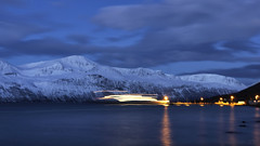 First ferry over the fjord (lunaryuna) Tags: norway northernnorway arcticregion tromsfylke ullsfjorden coast fjord lyngenalps mountainrange winter season seasonalwonders polarnight theremaininglight le longexposure ferry fergeroverlyngenogullsfjord fastferry lifeinthenorth lunaryuna landscape seascape sky clouds darkness