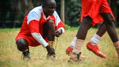 KENYA-C.2012 Young man crouches to adjust the laces of his footb (ChrisDortch) Tags: youth adjust adult africa african black cleats coach crouch field fitness fix foot football fun grass handsome kneel knees laces legs life man many men motion official outdoors padding people person play player playful several shin guards shoes soccer socks sport suit team teammates uniform unlace walk walking young