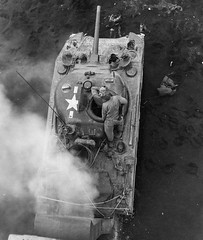 An M4 Sherman wading tank is seen mired in the mud on a a Normandy invasion beach. Note the raised air intakes for amphibious use.