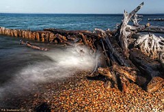 Waves Splashing Against a Groyne at Whitefish Point Michigan (PhotosToArtByMike) Tags: whitefishpoint michigan whitefishpointmichigan ndfilter mi lakesuperior paradisemichigan groyne groin wavebreaker post pier driftwood barricade shore upperpeninsulaofmichigan upperpeninsula up uppermichigan