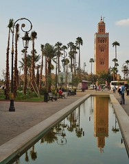 the symbol of Marrakech (SM Tham) Tags: africa morocco marrakech koutoubiamosque mosque islam building tower minaret park pool pond water reflections palms trees lampposts benches people sky garden plants flowers horsecarriage street vehicles outdoors