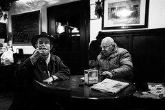 Freezing that moment in osteria (Giulio Magnifico) Tags: time style blackwhite 28mm wine vintage udine glasses osteria wood friuli freezing bw hat candid men leicaq bar leica streetphotography
