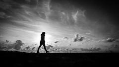 Walking alone - Howth, Ireland - Black and white street photography (Giuseppe Milo (www.pixael.com)) Tags: streetphotography howth silhouette ireland pier woman dublin clouds sky blackandwhite walking figure countydublin ie onsale faceless