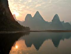 Sunset on Lijiang River (Pat Rioux) Tags: china sunset sun mountains reflection clouds river yangshuo lijiang