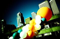 festive (poopoorama) Tags: seattle blue sky orange film buildings washington lomo lca xpro flickr meetup kodak turquoise crossprocess balloon e6 vignette e100vs whie flickrite pier52