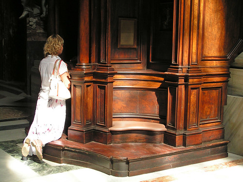 Photo of a woman kneeling at a confession booth.