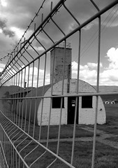 Behind the wire.... (Weddog) Tags: camp bw history training army scotland wire war nissan decay military perthshire creepy huts future ww2 pow deserted uncertain prisoner listed cultybraggan