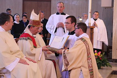 Deacon Kerins receives the Book of the Gospels.