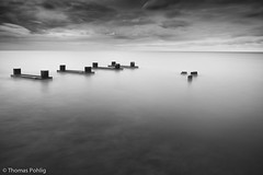 Disconnected (Thomas Pohlig) Tags: ocean longexposure light sunset sea blackandwhite water clouds landscape pier glow jetty fineart jersey series capemay pilings piling jerseyshore weatheredwood seashore oceanwaves shadw