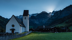 Sonne scheint durchs Martinloch zur Kirche (swissgoldeneagle) Tags: sun mountain mountains alps church berg sunrise switzerland kirche berge d750 alpen elm sonne sonnenaufgang glarus 16x9 martinsloch