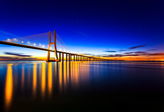 Fiery Reflections (One_Penny) Tags: longexposure morning bridge blue sky color portugal water architecture clouds sunrise reflections stars early colorful colours waterfront lisboa lisbon horizon ponte lissabon fiery iberia vascodagama pontevascodagama canon6d