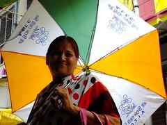 political undertones (s) Tags: india smile umbrella streetphotography grin strike kolkata calcutta streetshot bandh kalighat desertedstreets politicalumbrella
