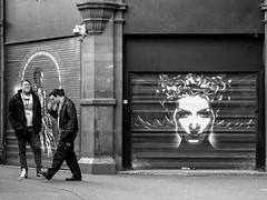 Northern Quarter #157 (Peter.Bartlett) Tags: manchester eyecontact graffiti art unitedkingdom urbanarte people peterbartlett facade doorway noiretblanc streetphotography standing smoking shutter lunaphoto man urban olympuspenf candid uk m43 microfourthirds niksilverefex bw monochrome wall blackandwhite city men