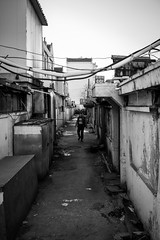 Not really welcome (Go-tea 郭天) Tags: old narrow alley dark winter cold sun sunny shadow wired man qingdao huangdao mess messy cables electric houses buildings alone lonely welcome no walk walking movement out meet meeting greeting water floor adventure not happy unhappy street urban city outside outdoor people bw bnw black white blackwhite blackandwhite monochrome asia asian china chinese shandong canon eos 100d 24mm prime lantern light electricity