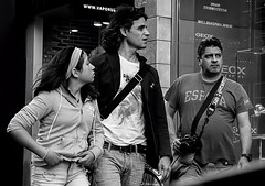 The Explorers (Szoki Adams) Tags: montreal downtown tourists spanish trio intense moving photographer camera eyeglasses younggirl motion staring adjusting focused serious mobile blackandwhite bw blackwhitephotos monochrome streetphotography street streetphoto canong15 candid energetic friends girl men hairflying store urban unaware walking expressive