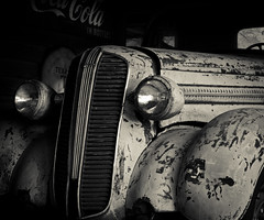 Death by Neglect (hutchphotography2020) Tags: monochrome neglect rust antiqueauto garage headlights louvres grill fenders nikon blackandwhite hutchphotography