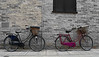 2 Bicycles (Travis Pictures) Tags: cambridgeshire cambridge drummerstreet bikes bicycles cycle city cityscape citycentre purple wall bricks outdoors outside selectivecolour nikon d5200 photoshop summer blackandwhite eastanglia fenland fens england britain uk transport cambs