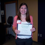 A student posing with her Honorable Mention Research Poster award.