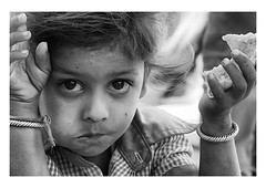 a mouthful of bread (handheld-films) Tags: travel school portrait people blackandwhite food india girl monochrome closeup female rural children bread eyes education faces eating indian documentary portraiture rajasthan subcontinent