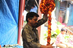 Winding it up (bluelotus92) Tags: orange india flower focus market sale maroon flowervendor karnataka mysore marigold flowerseller mysuru devarajursmarket devarajaursmarket flowerwinding
