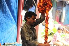 Winding it up (bluelotus92) Tags: orange india flower focus market sale maroon flowervendor karnataka mysore marigold flowerseller mysuru devarajursmarket devarajaursmarket flowerwinding