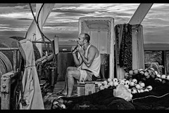 the egyptian (dim.pagiantzas   photography) Tags: fisherman shaving boat caique nets sea seascape seaside sky clouds cloudy people man male egyptian sailor gunwale metal iron blanket outdoor canon grayscale monochrome
