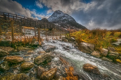 Troubled waters (Lee~Harris) Tags: water watercourse waterways watermotion longexposure bridge architecture rugged rural rocks grass outdoors outdoor wales snowdonia ogwenvalley mountain mountains snowcappedmountain light nikon nikond300 landscape landscapes landscapephotography scenery scene