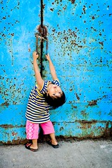 hanging out a blue door (phitar) Tags: door blue color girl indonesia child 2006 jakarta topf100 pinkpants phitar