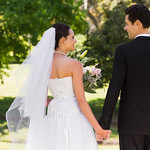 Newlywed couple holding hands and walking in park thumbnail