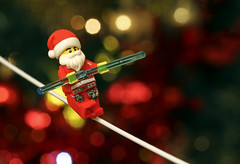 Santa's Balancing Act (Skyline:)) Tags: flickrfriday balance santa fatherchristmas tightrope red yellow golden green bokeh 7dwf