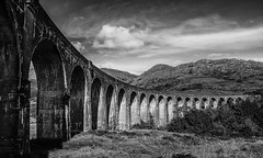 the mark of man in nature (lunaryuna) Tags: scotland highlands glenfinnan glenfinnanviaduct railway valley landscape architectureinlandscape bridge bridingthegap mountain swerve arches perspective sky clouds blackwhite bw monochrome lunaryuna ngc