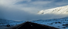 Driving Off The Edge (Brian Travelling) Tags: weather snow storm clouds cloud bluesky mountains mountain road whitelines roadmarkings blacktar rugged white blue sunshine