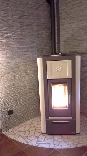 Stufa termopellet con pavimento palladiana e rivestimento in grès porcellanato effetto pietra