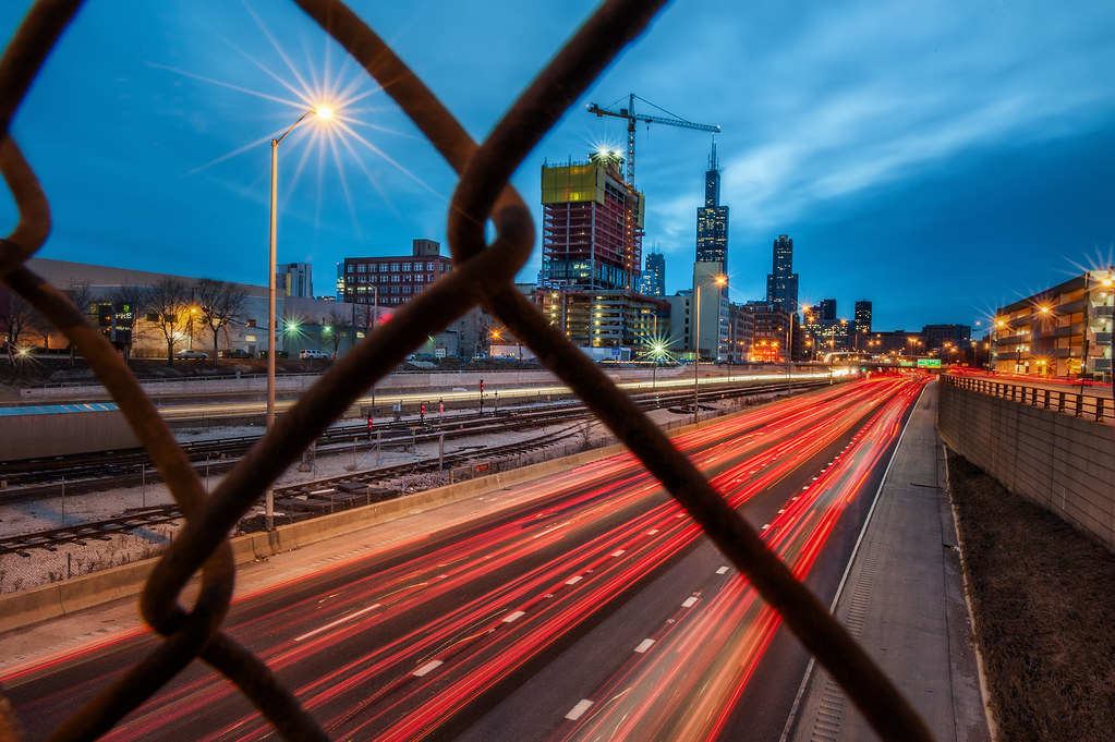 The Eisenhower Expressway from behind a chain link fence on Morgan Street.