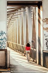 Crossing Over (Doug Knisely) Tags: street bridge light sunset panorama woman sunlight grafitti crossing shadows pano olympus 7518 omdem5markii