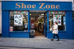 Shoe Zone (Howie Mudge LRPS) Tags: shoezone aberystwyth woman person shop window door pavement sign windows signs shoes road walk walking outside outdoors travel travelling traveler ceredigion wales cymru uk street streetphotography streetlife streetstyle blue fuji fujifilm xt1 fujifilmxt1 fujixt1 xf27mmf28 classicchrome