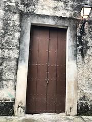What type of stone is this sloping doorway nestled in?  (Havana, Cuba) (lcncrtr) Tags: mystery leaning diagonal portals fantasy entrances streetlamp closed old habana door padlock iphone7 doors cuba havana