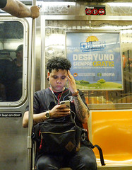 Subway Passenger (UrbanphotoZ) Tags: man sitting subway tattoos curls chicagobulls smartphone earholes poster schoolfoodnycorg breakfast schoolmeals desayuno siempre gratis reflection manhattan newyorkcity newyork nyc ny