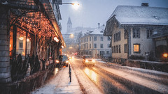 Driving on a snowy evening (VandenBerge Photography) Tags: travel car lights snow cityscape city thun berneseoberland switzerland europe winter road building street streetscene season romantic evening driving weather atmosphere streetlight streetview