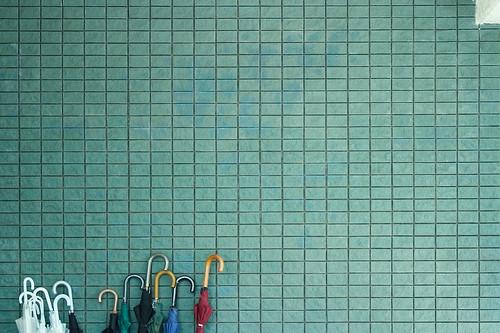 Fotografía de de una pared de gresite verdosa con unos paraguas en la parte inferior izquierda