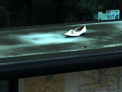 Shoes In Strange Places 2 (Lady Vervaine) Tags: street city uk england urban white bus london contrast dark lost shoe one alone shine darkness britain surreal busshelter single shining fairytalesdarkly shoesinstrangeplaces werestillnotinkansasimafraid