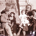 Grandfather Max Thomson with Jill Grace, Nana Vera Thomson (Nee Collins) with Margaret Grace and Nan Grace seated on wall.