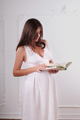 Pregnant woman with book (GrasePhoto.) Tags: pregnant woman girl white caucasian brunette stand dress beautiful young twenty slim belly longhair one studio people interior home lookdown busy book read page pretty portrait