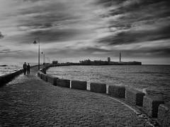 Cadiz pier - Castillo de San Sebastian (Marcelo Garcia Ferreyra) Tags: bnw black white pier sea castillo san sebastian cadiz spain europe couple waves clouds castle de lighthouse curve stone sunset